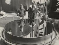 "John D. Strong & Enrique Gaviola looking into the freshly aluminized 100"" mirror"