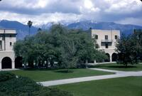 View of Gates Laboratory of Chemistry (left) and Dabney Hall with connecting portales, with 400-year-old Engelmann oak in foreground and snow-capped San Gabriel mountains behind.